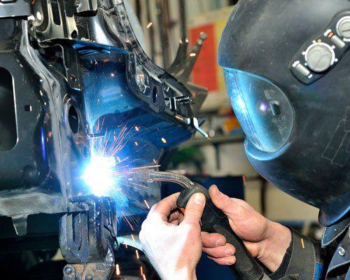 meccanico che ripara un'auto con saldatore