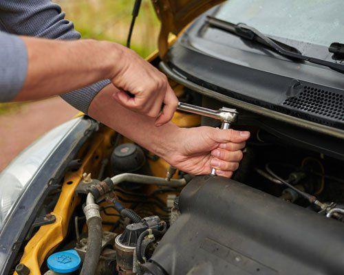 persona che ripara il motore di un'auto