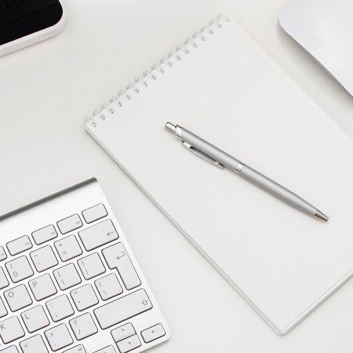 agenda con penna vicino a una tastiera