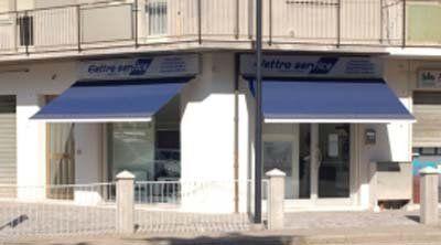 vista esterna del negozio ELETTROSERVICE con due tende parasole