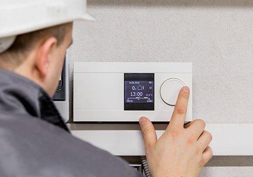 operaio controlla un termostato