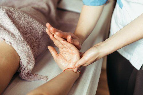 fisioterapista mentre tratta un paziente con problemi alla mano