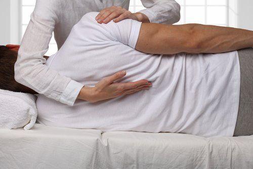fisioterapista mentre tratta un paziente di schiena