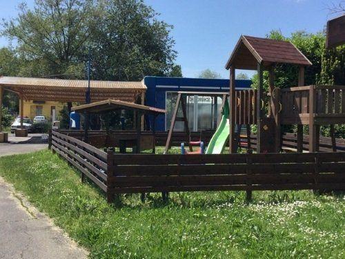 un recinto di legno con uno scivolo e altri giochi