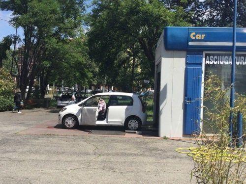 una macchina bianca con la portiera aperta vicino a un autolavaggio