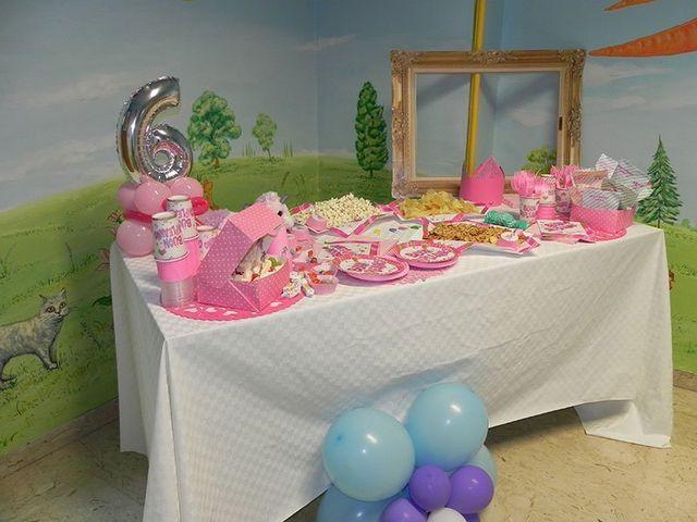 Tavola lunga decorata per un compleanno, con tovaglia bianca, palloncini, bicchieri, posate e piattini in plastica di colore rosa