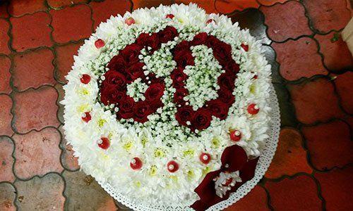 Un bouquet di fiori di color bianco e raffigurazione del numero 60 con delle rose di color rosso