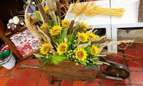Una carriola di legno usata come un vaso e dentro dei fiori girasole