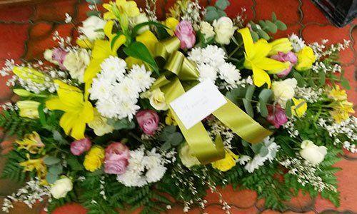 Un bouquet di fiori di color rosa, bianco, giallo e delle foglie verde