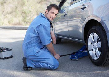 A mechanic working under a car on ramps