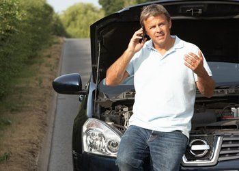 A man sitting on the open bonnet of his car in a country lane, calling a breakdown service on his mobile phone