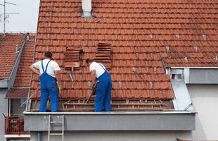 Two men working on fixing a roof