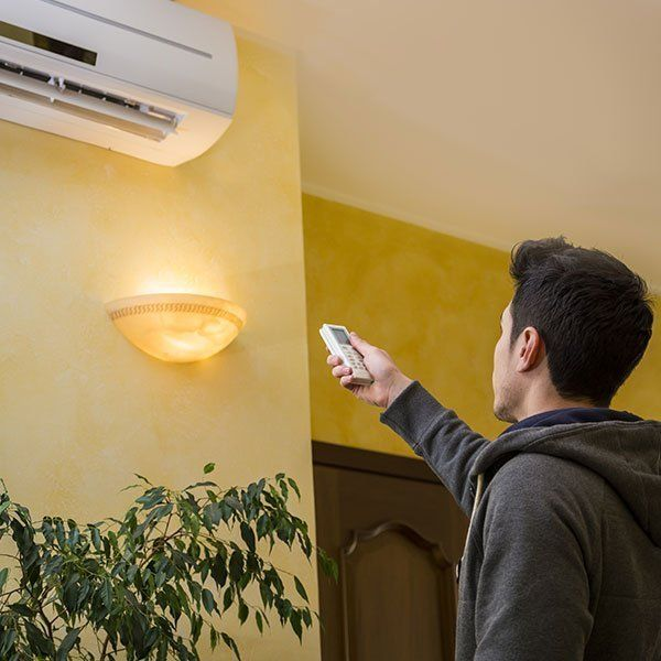 man turning on air conditioning unit