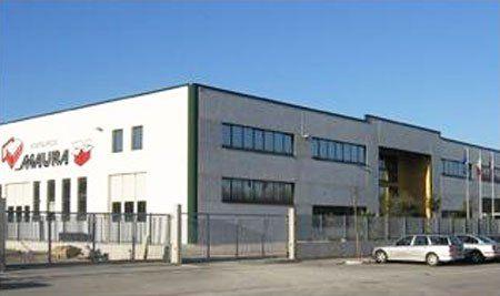 Una stabile grande con scritto Maura in grande sulla facciata e alcune macchine parcheggiate davanti