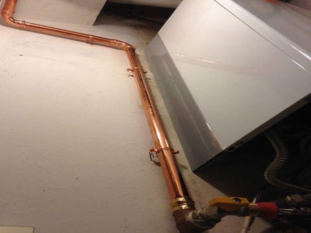 un tubo di rame di un impianto termico attaccato a una caldaia