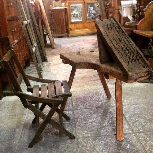 una sedia di legno e un tavolo in un negozio di antiquariato