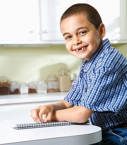 boy smiling missing teeth