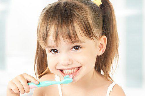 small girl brushing teeth