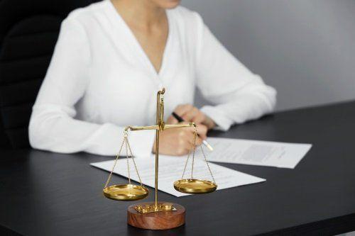 una donna con un golf bianco seduta alla scrivania e una bilancia a due piatti