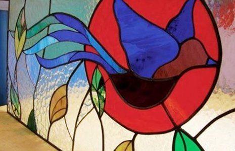 una vetrata con dei disegni di alcune foglie verdi e dei disegni astratti color blu e rosso