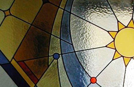una vetrata a colori rosso,beige e giallo e il disegno di un sole giallo