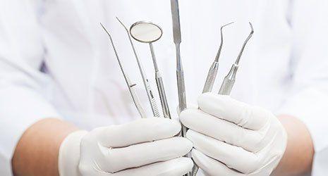 Due mani che mantengono strumenti da dentista