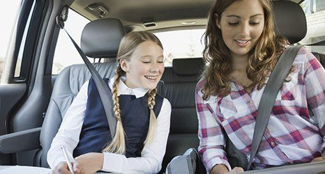a girl doing homework in a car