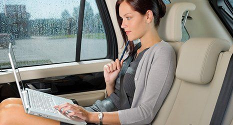 A women sitting in a car working on laptop