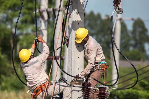 degli elettricisti con degli elmetti al lavoro su un palo della luce con dei cavi a vista
