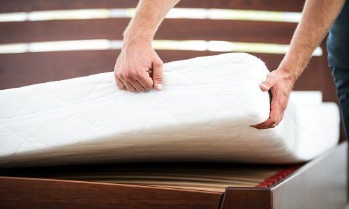 due mani che sollevano un materasso