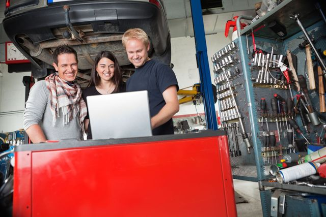 A mechanic resetting a car system with a laptop