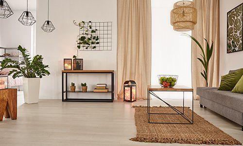 un salotto con delle lampade a sospensione, un tavolino e sulla destra un divano