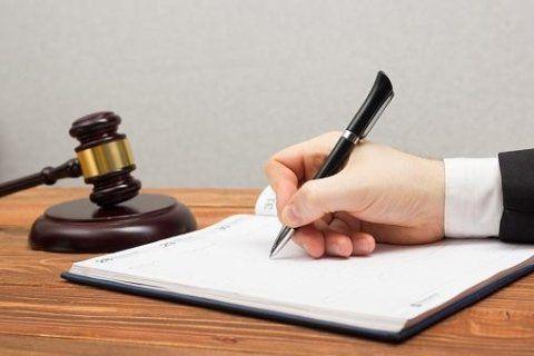 Mano scrivendo e un martello di giustizia