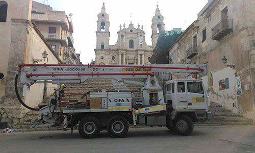 un camion bianco da lavoro in una strada con vista di una chiesa