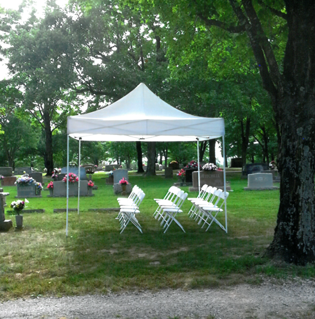 A large white party tent with red stripes on a lawn