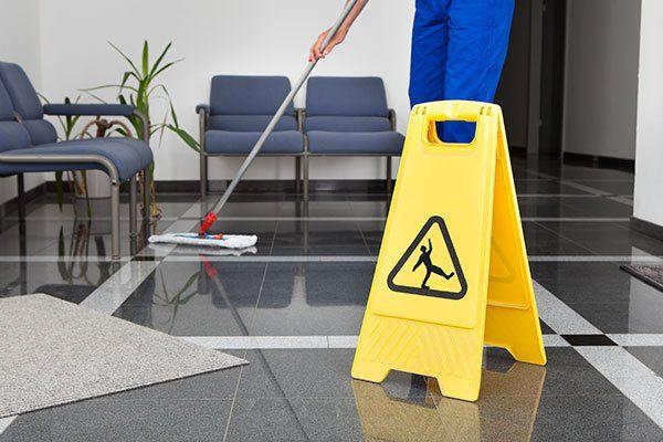 pulizia di pavimenti di sala d'attesa con segnale di pavimento bagnato