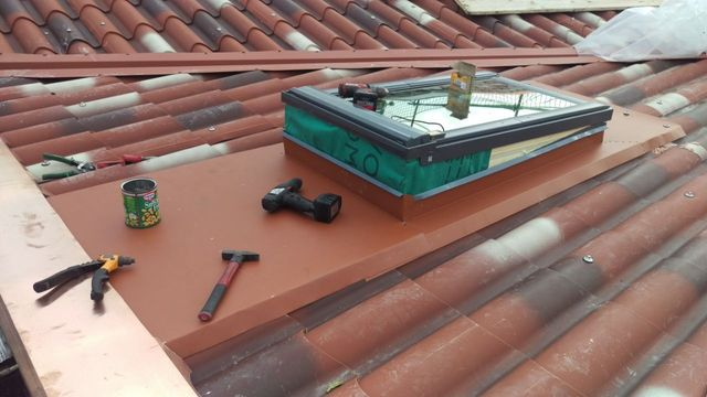 finestra sul tetto in costruzione con un trapano e un martello lì vicino