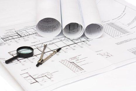 lente ingrandimento e compasso su progetto di edificio a Vignolo
