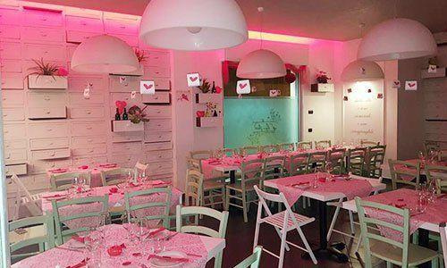 vista dei tavoli all'interno del ristorante con delle luci rose