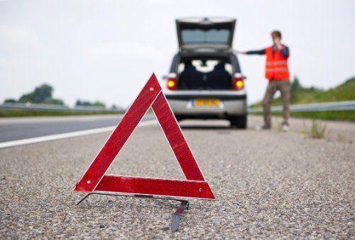 un triangolo e davanti una macchina in panne e un uomo al telefono