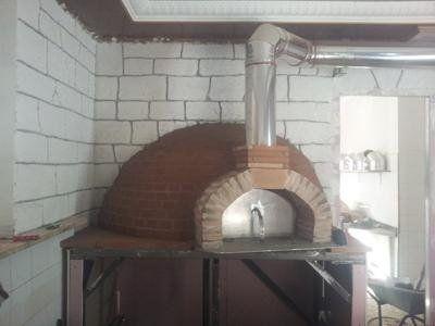 un forno con mattoni a vista e una canna fumaria in acciaio