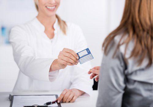 Donna mentre consegna una carta assicurativa al cliente