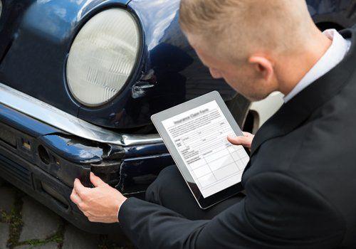 Uomo mentre controlla una macchina incidentata