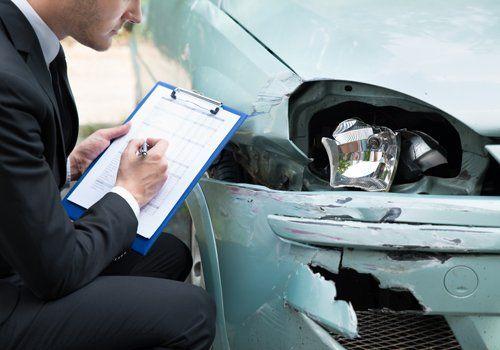 consulente assicurativo mentre valuta il danno ad un auto a seguito di un incidente stradale