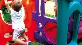 bambino mentre si arrampica dentro un gioco di un asilo
