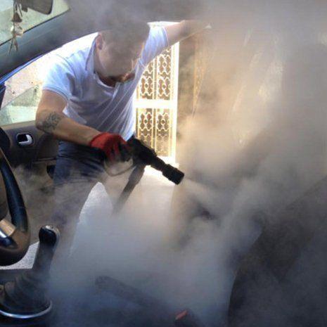 un ragazzo che sta usando una pistola nera che emette vapore su un sedile all'interno di una vettura