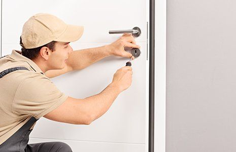 Male locksmith installing a lock on a new door with a screwdriver