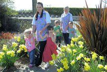 Two of our carers leading children through the daffodils in the garden