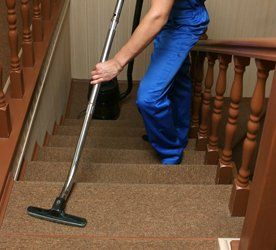 A flight of carpeted stairs being hoovered