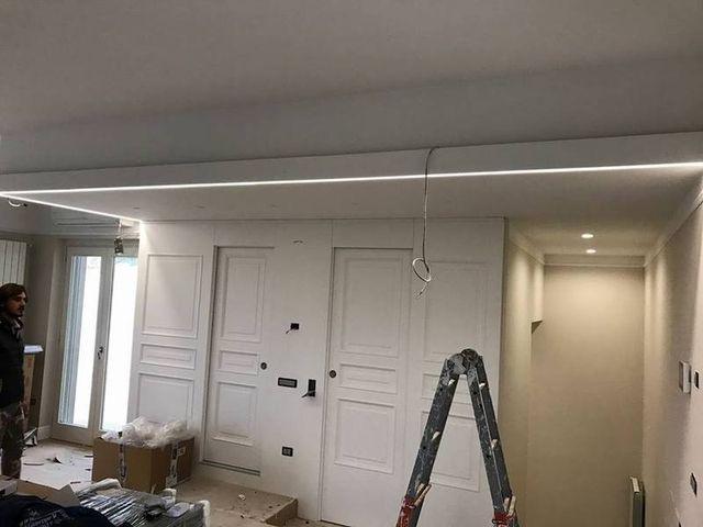 una scala da lavoro in un appartamento e un filo che pende dal soffitto